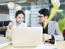 Asian business man and woman working together in office Royalty Free Stock Images