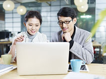 Asian business man and woman working together in office Stock Photos