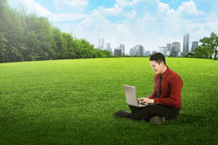 Asian business man working with laptop and sitting on the grass Royalty Free Stock Image
