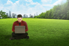 Asian business man working with laptop and sitting on the grass Royalty Free Stock Images