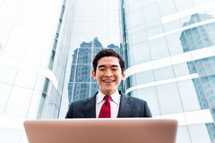 Asian business man working outside on computer Stock Image