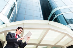 Asian business man working outside on tablet PC Stock Image
