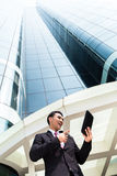 Asian business man working outside on tablet PC Royalty Free Stock Image