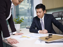Asian business people. Manager reviewing business with subordinate in office Stock Photo