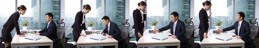 Asian business people. Manager reviewing business with subordinate in office Royalty Free Stock Image