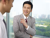 Asian business people. Asian businessman standing and talking in office Stock Photography