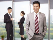 Asian business people. Portrait of a senior business executive with his colleagues in the background Royalty Free Stock Photos