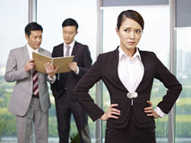 Asian business people. Portrait of a young asian businesswoman with her colleagues in the background Stock Photos