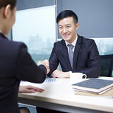 Asian business people. Asian business executives shaking hands in office Stock Photos