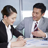 Asian business people. Asian business executives discussing business in office; focus on the man Royalty Free Stock Image