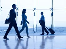Asian business people in airport terminal building. Asian business people walking in airport terminal building, focus on the background stock photos