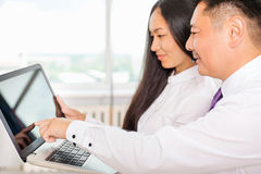 Asian business people analyze work on laptop at office Royalty Free Stock Photo