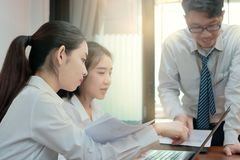 Asian business people brainstorming together in office. Selective focus and shallow depth of field. Asian business people brainstorming together in office royalty free stock image
