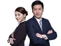 Asian business people. Asian businessman and businesswoman standing back to back, arms crossed Stock Photography