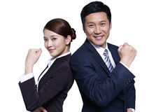 Asian business people. Asian businessman and businesswoman standing back to back, making a fist Royalty Free Stock Image