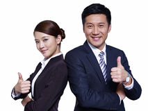 Asian business people. Asian businessman and businesswoman standing back to back, thumbs up Stock Images
