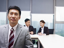 Asian business people. Asian businessman praying for help in office Royalty Free Stock Images
