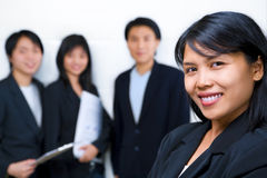 Asian business people with businesswoman in front Stock Photo