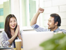 Asian business people celebrating success in office Stock Photo