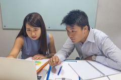 Asian business people discuss about work on laptop royalty free stock image