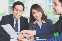 Asian business people discussing document in a meeting Royalty Free Stock Image