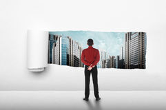 Asian business people looking the city from paper tear Royalty Free Stock Image