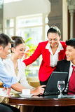 Asian business people at meeting in hotel lobby Royalty Free Stock Photos