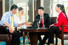 Asian business people at meeting in hotel lobby Stock Image