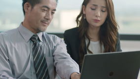 Asian business people meeting in office. Two asian corporate executives discussing business in office using laptop computer stock footage