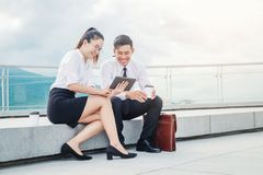 Asian business people meeting and using digital tablet outdoor after work royalty free stock image