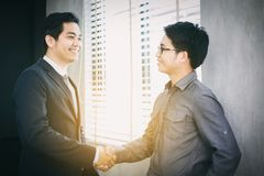 Asian Business people shaking hands and smiling their agreement Stock Image
