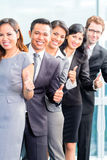 Asian business people standing in row in office Stock Images