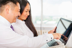 Asian business people using laptop at office Stock Photo