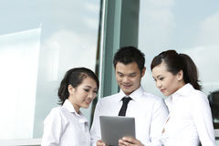 Asian business people using touch-pad tablet Royalty Free Stock Images