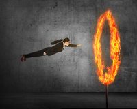 Asian business person flying through ring of fire. Business risk conceptual Stock Photo