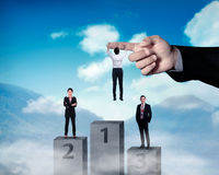 Asian business person hanging on the large hand Royalty Free Stock Photo