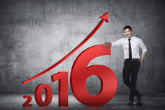 Asian business person lean next to 2016 number. New year resolution concept Royalty Free Stock Photography