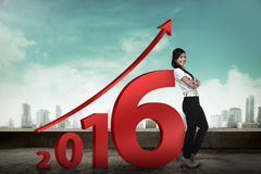 Asian business person lean next to 2016 number. New year resolution concept Royalty Free Stock Photos