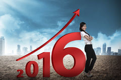 Asian business person lean next to 2016 number. New year resolution concept Royalty Free Stock Image