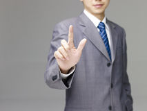 Asian business person pushing a virtual button. Young asian business person in suit pushing a virtual button, gray background Royalty Free Stock Photo