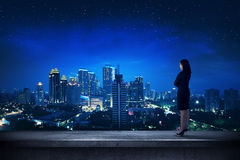 Asian business person standing on the rooftop. Looking the city Stock Image