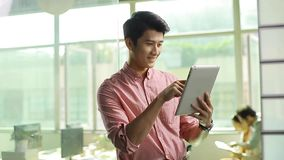 Asian business person using tablet. Young asian corporate executive using ipad in office stock footage