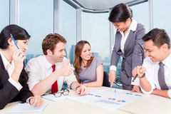 Asian Business team discussing charts Royalty Free Stock Images