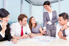 Asian Business team discussing charts Stock Photos
