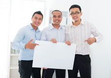 Asian business team holding a blank banner. Southeast Asian business team holding a blank banner in office Stock Image
