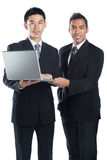 Asian Business team partners. Two Asian businessmen, Chinese and Malay, holding a laptop together signifying racial harmony and international, regional Stock Image