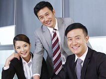 Asian business team. A team of asian business people looking at camera and smiling Royalty Free Stock Images