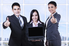 Asian business team showing blank screen on laptop. And thumbs up Royalty Free Stock Photos