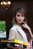Asian business woman. Is holding yellow and black business files Stock Image