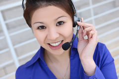 Asian Business Woman. An asian customer service employee thinking and listening to the client Stock Images